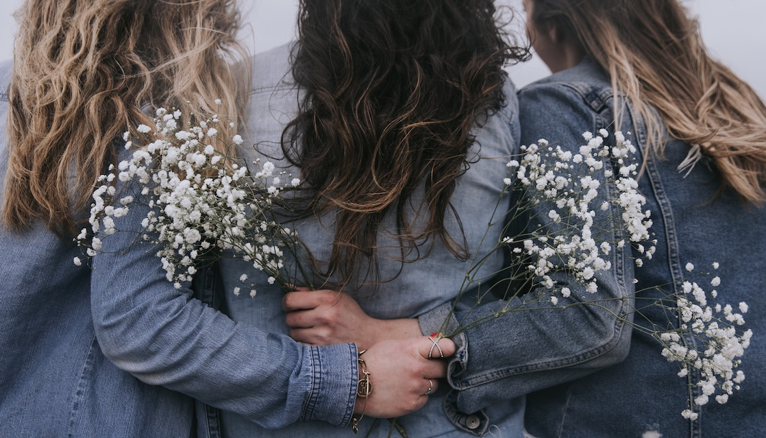 Three Women Arm In Arm With Flowers
